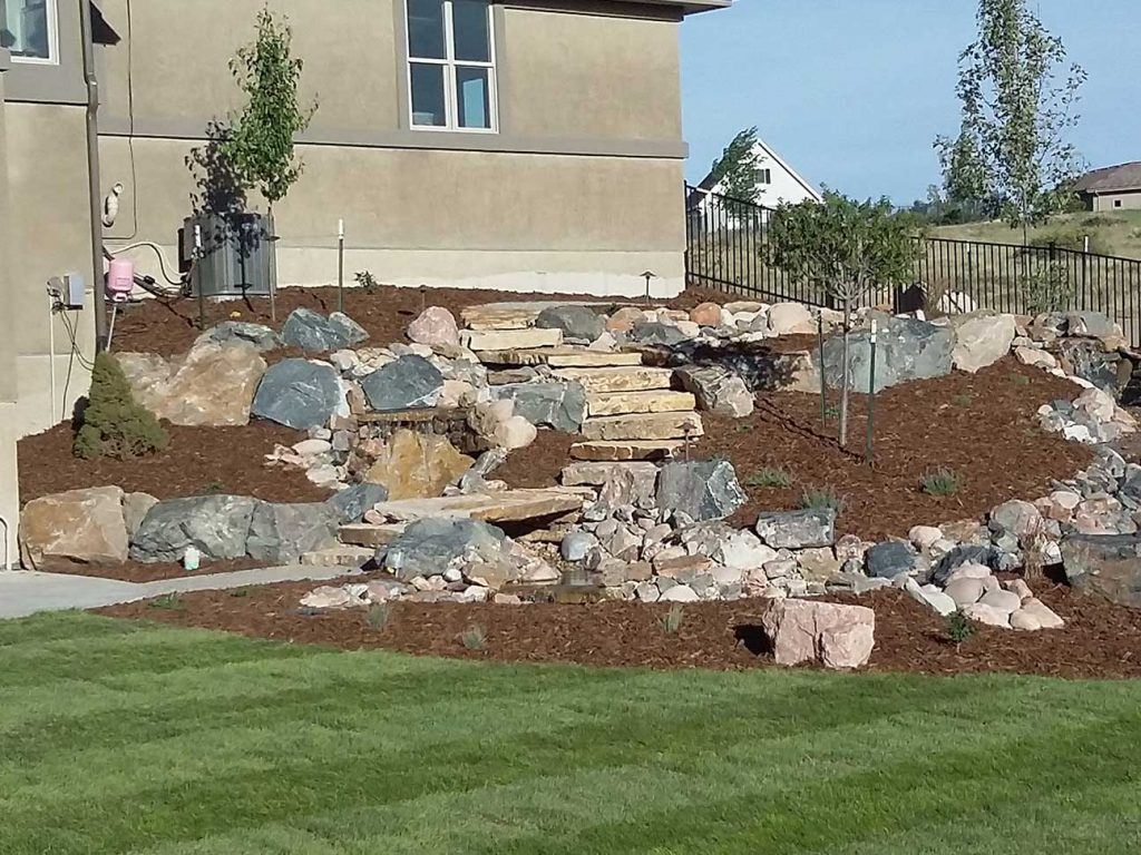 landscape design denver rock wall with grass and mulch